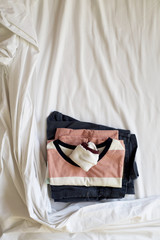 folded clothes on an unmade bed