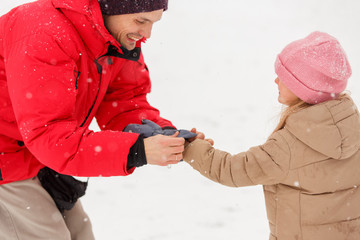 Image of his father dressing daughter mittens in winter park