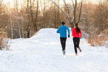 Photo from back of running two athletes in winter park