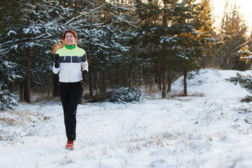 Image of brunette athlete in sneakers on morning run against tree in winter