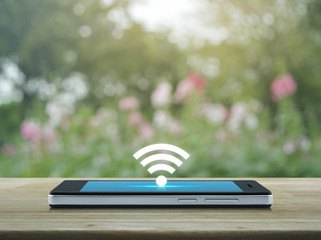 wi-fi button flat icon on modern smart phone screen on wooden table over blur pink flower and tree, Technology and internet concept
