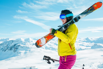 Photo of girl wearing helmet, mask with skis on her shoulder