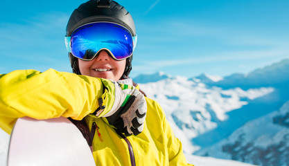 Image of smiling girl in helmet and mask with snowboard on background of snowy hills