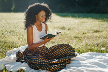 Outdoor sunny picnic. Adorable young african girl with green eye shadows is resting while reading the book.