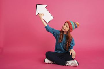 Cheerful girl looking up and holding arrow up isolated