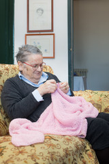 Elderly woman knitting pink wool on sofa smiling at home portrait