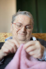 Elderly woman knitting pink wool selective focus on smiling face