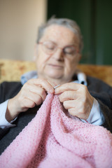 Elderly woman knitting pink wool selective focus on hands