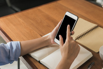 Young woman using smartphone mock up blank black screen while she working in the shop covered on a warmlight day. Young woman swipe her smartphone in a shop. indoor working in a house concept.