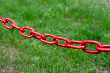 Iron red chain on a background of green grass