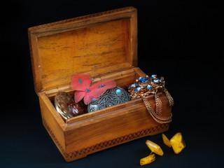 Old wooden box with broken ornaments on a black background