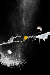 Egg in flight, milk and flour on black background. Scattering egg shells