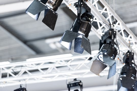 Lights attached to aluminium truss pointing down in a big exhibition hall