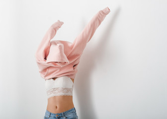 Young woman dressing pink hoody. White background. Copy space.