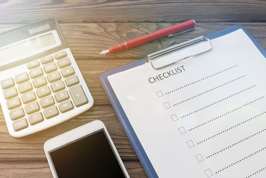 check sheet. calculator, smartphone on a wooden background. business, questionnaire, list.