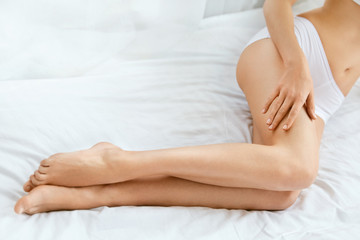 Long Woman Legs. Female With Smooth Legs And Body On Bed.