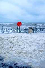 seafront promenade in a storm, foam from the sea all over the promenade, red life bouy and large waves with white foam on the sea