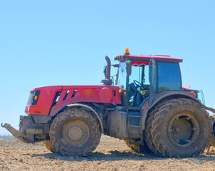 Red modern tractor on the field