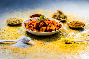Traditional/regional carrot pickle,Daucus carota subsp. sativus pickle with ingredients like red pepper powder and turmeric powder with ginger garlic paste on a silver wooden floor.