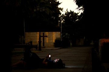A man uses a mobile phone as he attends a movie screening in a cemetery as part of 'Ghost Tour' heritage circuit, in Santiago