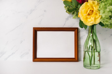 Wooden photo frame mockup, beautiful bouquet of flowers in glass vase in front of pale marble background