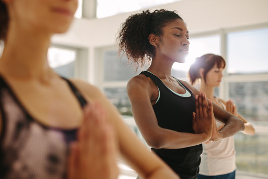 Woman practice yoga with friends in gym