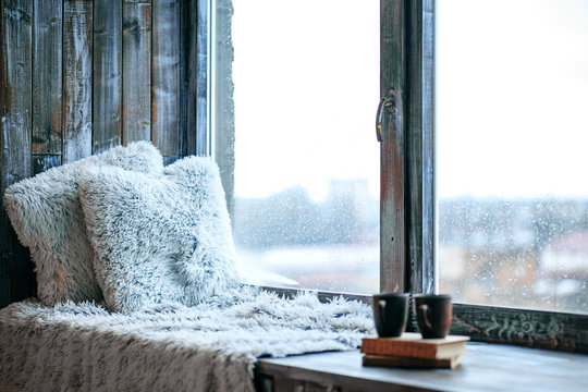 Large window with a window sill. Blankets and books. The concept of rest, relaxation, reading.