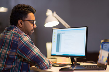 creative man working with laptop at night office