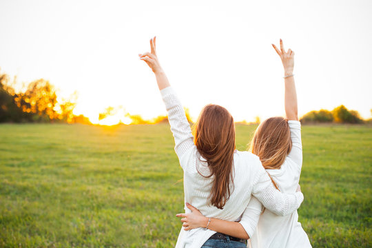Two women in white sweaters are looking on the sunset. Best friends