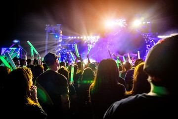 Many people are in local concert and all they standing in front of the stage. The audience in silhouette photo style. Many people are in the music festival event.