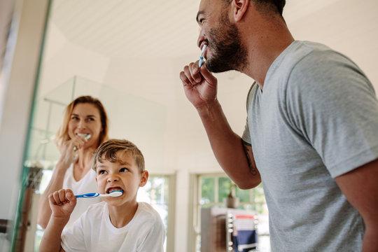 Family brushing teeth together in bathroom