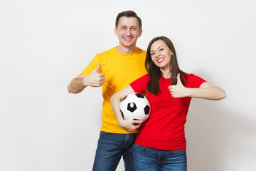 Fun smiling cheerful young couple, woman, man, football fans in yellow and red uniform cheer up support team holding soccer ball isolated on white background. Sport, family leisure, lifestyle concept.