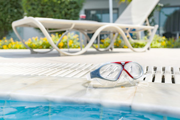 glasses for swimming on the edge of the pool on a beautiful sunny day