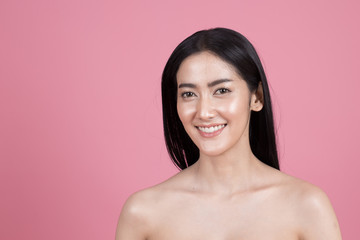Beautiful Asian Woman Portrait. Beautiful Woman looking to camera. Woman show her beautiful face. People with youth and skin care concept. Isolated on pink background.