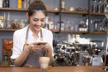 Asian barista woman using smartphone for take coffee pictures. Woman using smartphone with attractive smiling.