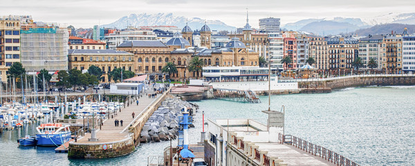 Panorama of San Sebastian (Donostia) in cloudy winter day with the snowy mountains on horizon.