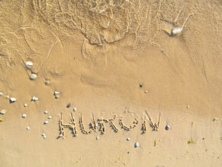 Hand drawn word -Huron- on sandy beach. Horizontal view close up detailed image of text, sand and lake water.