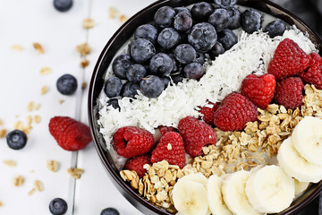 Healthy Breakfast Buddha Bowl with berries, coconut, bananas and granola.