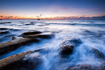 scenic view of sunset seascape with rocks covered by green moss on the ground. image contain soft focus due to slow shutter.