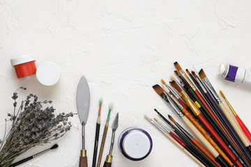 Professional brushes for artists, palette knives, colorful paints and dried lavender branches lie on a white canvas