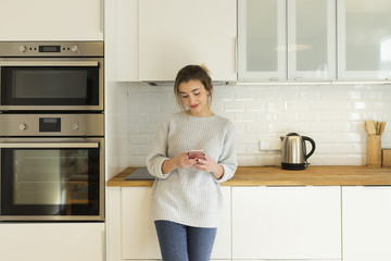 Young woman using a smart phone while standing in the kitchen