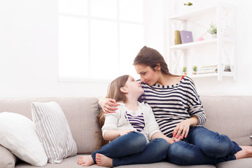 Mother with her cute little daughter sitting on the sofa.