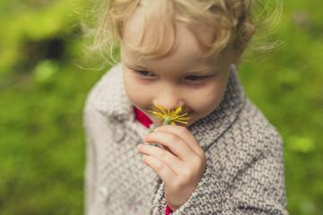Cute girl smelling flower on field