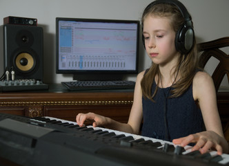 Little girl recording a song in home music studio.