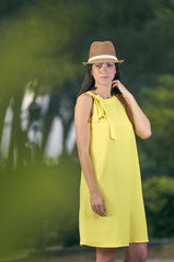 Attractive and fashionable young woman with a yellow dress in nature