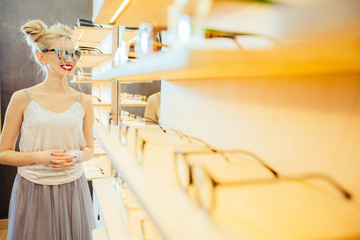 Young fashion woman with red lips and funny hairstyle choosing eyeglasses in optical store - Beautiful girl wearing sunglasses in optician shop. Ophthalmology concept.