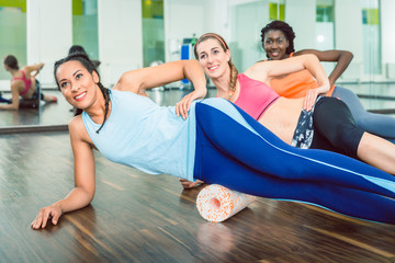 Beautiful fit woman smiling while wearing blue fitness sleeveless top and leggings during group workout class of foam rolling at the gym