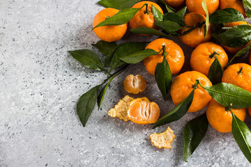 Tangerines with green leaves close up on light background