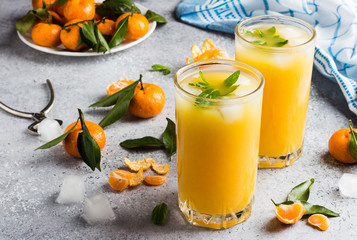 Tangerine juice in glasses on light background