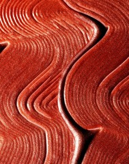 Close up of wavy line pattern in red liquid makeup